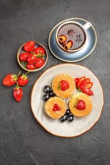 Vista dall'alto piccole frittelle gustose con frutta e tazza di tè sulla superficie grigia torta torta di frutta