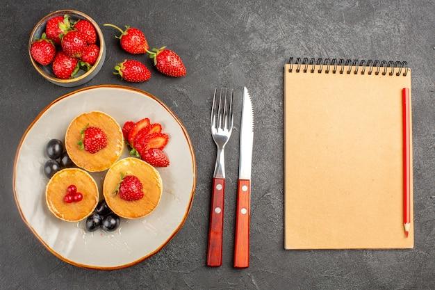 Vista dall'alto piccole frittelle gustose con frutta su frutta torta torta scrivania grigio scuro