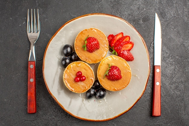 Top view little yummy pancakes with fruits on dark-grey surface pie cake fruit