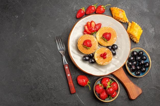 Vista dall'alto piccole frittelle gustose con frutta sulla torta di frutta torta superficie scura
