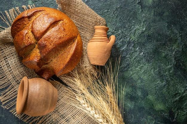 Vista dall'alto di una pagnotta di pane nero dietetico su asciugamano marrone e ceramiche sul lato destro su sfondo di colori scuri