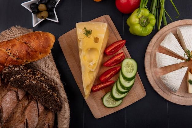 Vista dall'alto pagnotte di pane nero in un cesto con maasdam e formaggio feta e pomodori cetrioli su un supporto su uno sfondo nero