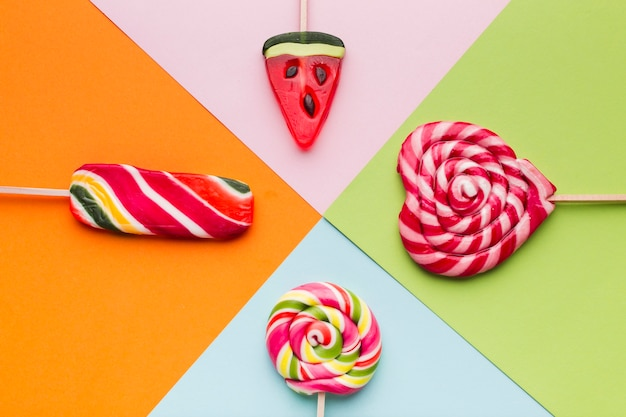Top view lollipops on colorful table
