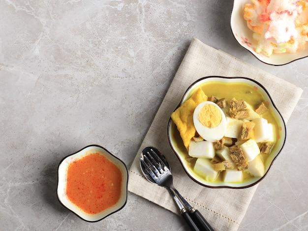 上面図ロントンカリサピまたはインドネシアのビーフカレーとライスケーキ。インドネシアの西ジャワで朝食に人気の屋台の食べ物。コピースペース