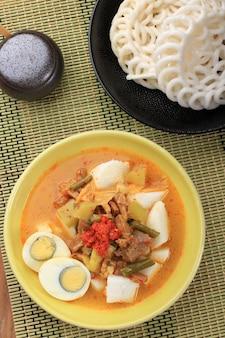 Вид сверху лонтонг саюр паданг, овощное карри с рисовым пирогом, подается с вареным яйцом
