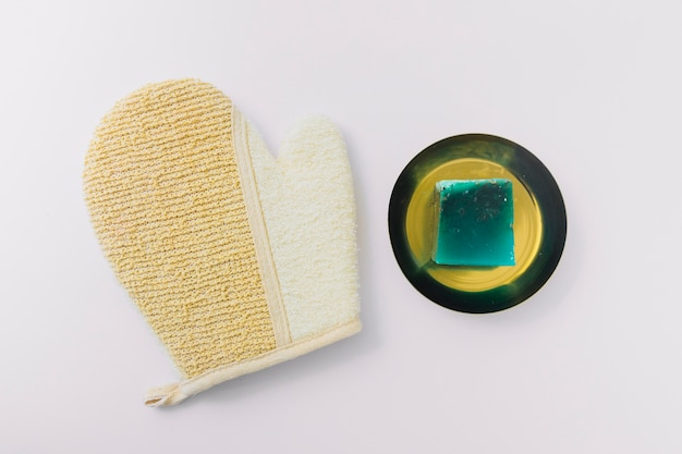 Top view of loofah mitt and green soap bar on plate isolated over white background