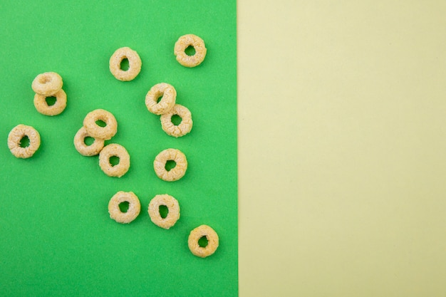Top view of loop and healthy cereals on green surface and yellow background