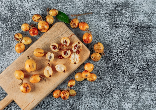 Top view loquats on cutting board on gray textured background. horizontal space for text