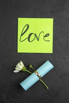 녹색 스티커 메모 약혼 반지 꽃에 쓰여진 상위 뷰 사랑 어두운 배경에 스티커 메모를 말아서