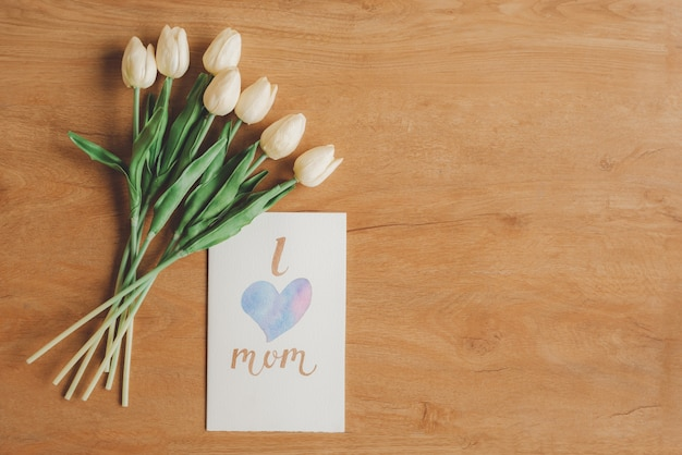 Top view of lovely greeting card i love mom and flowers on wooden background