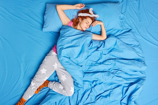 Top view of lovely redhead teenage girl sleeps deeply on comfortable bed in funny pose on back sees pleasant dreams wears pajama stretches arms and legs. cozy bedtime and good sleep concept.