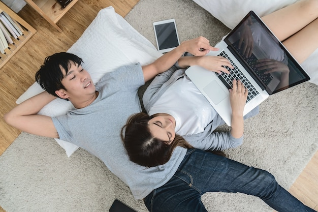 Top view of lover using the digital tablet at modern home sleeping on the carpet floor
