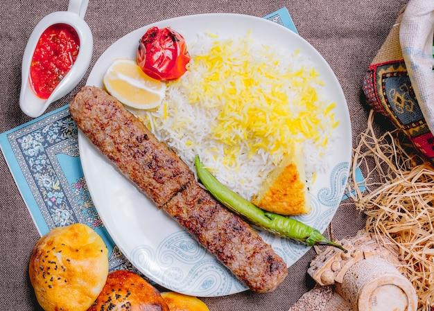 Вид сверху люля-кебаб с рисовыми помидорами и зеленым перцем на гриле с ломтиком лимона и соусом