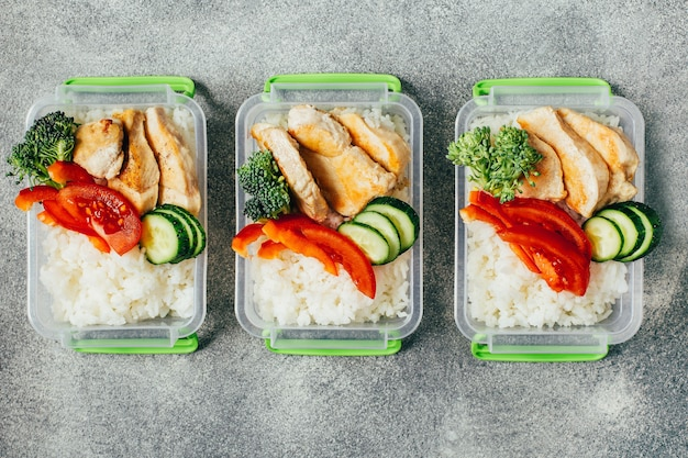 Top view of lunch boxes with food rice meat vegetables and fruits centered on gray surface