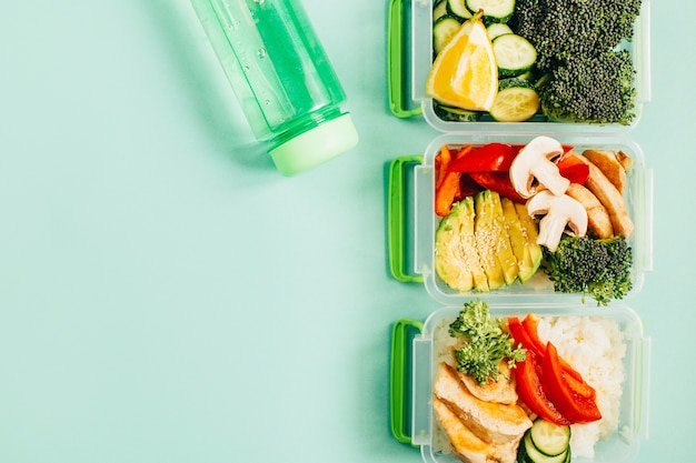 Top view of lunch boxes with food rice meat vegetables and fruits on green background with free space for text