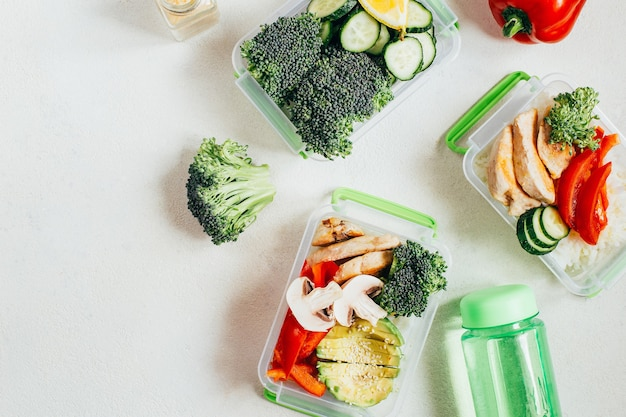 Top view of lunch boxes with vegetables, rice, meat on gray surface