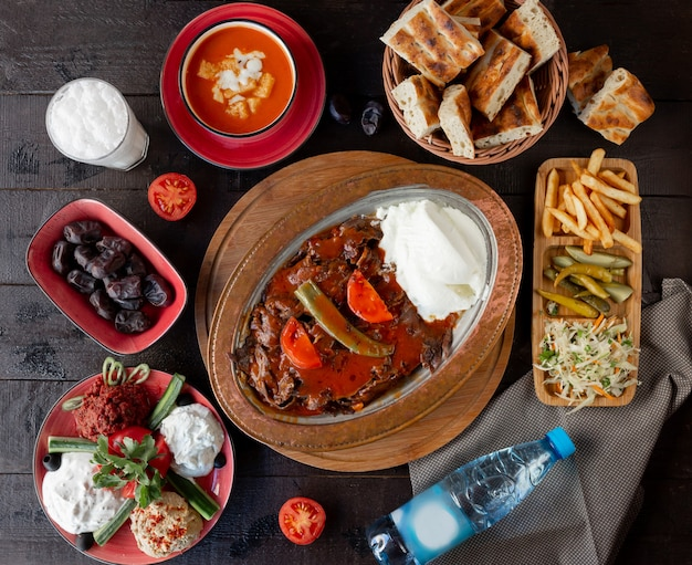 Top view of lunch setup with iskender kebab, tomato soup, pickles, turkish meze