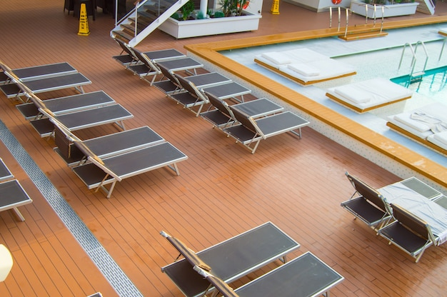 Top view of the luxurious pool with empty sun beds on the open deck of a modern cruise liner