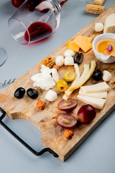 Top view of lying glass of red wine with different kinds of cheese grape olive nuts butter on cutting board and cork on white 1