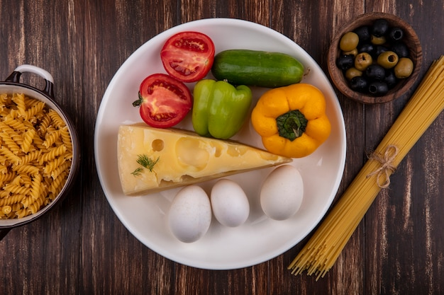 Top view maasdam cheese with chicken eggs  tomato  cucumber and bell peppers on a plate with olives  raw spaghetti and pasta on a wooden background