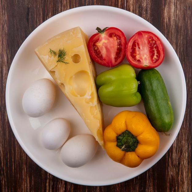 Vista dall'alto di formaggio maasdam con uova di gallina, pomodoro, cetriolo e peperoni su un piatto su un fondo di legno