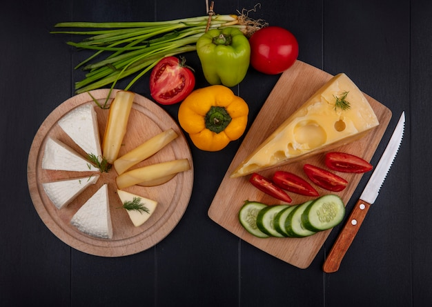 Top view maasdam cheese with tomatoes and cucumbers on a board with a knife and feta cheese with bell peppers and green onions on a stand  on a black background