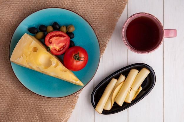 Vista dall'alto di formaggio maasdam con pomodori e olive su un piatto blu con una tazza di tè e formaggio affumicato su un piatto bianco