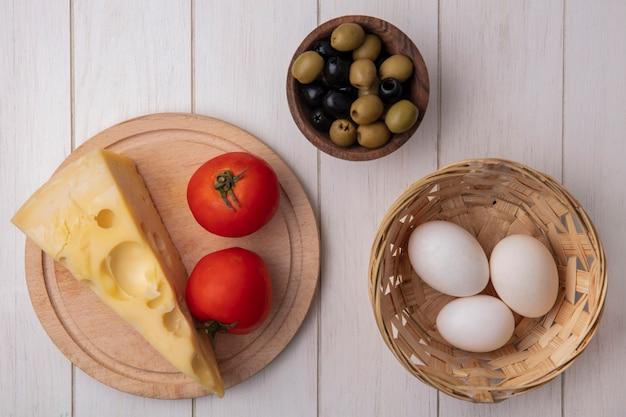 Vista dall'alto formaggio maasdam con pomodori su un supporto con olive e uova di gallina in un cesto su uno sfondo bianco