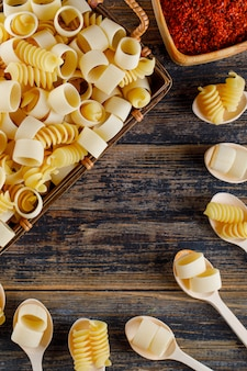 Top view macaroni pasta in basket and spoons with red spice on wooden background. vertical