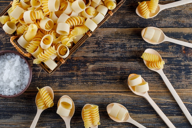 Top view macaroni pasta in basket and spoons with salt on wooden background. horizontal