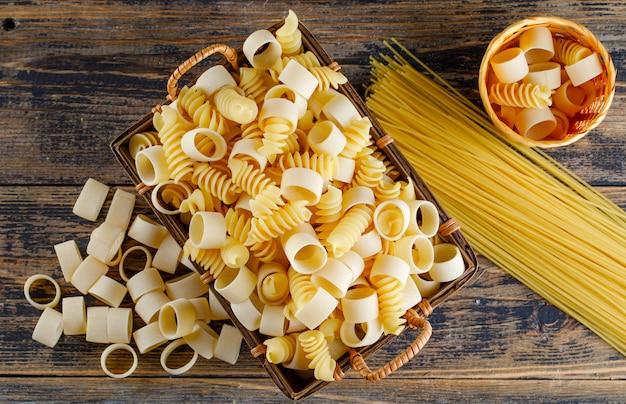 トレイと木製の背景にスパゲッティと小さなバケツで平面図マカロニパスタ。横型