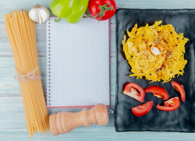 Top view of macaroni pasta and sliced tomato in plate with raw ingredients