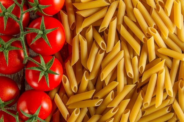 Top view of macaroni next to tomatoes