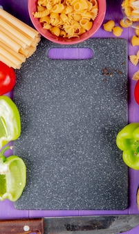 Top view of macaronis as bucatini rotini and others with pepper tomato knife around cutting board on purple background