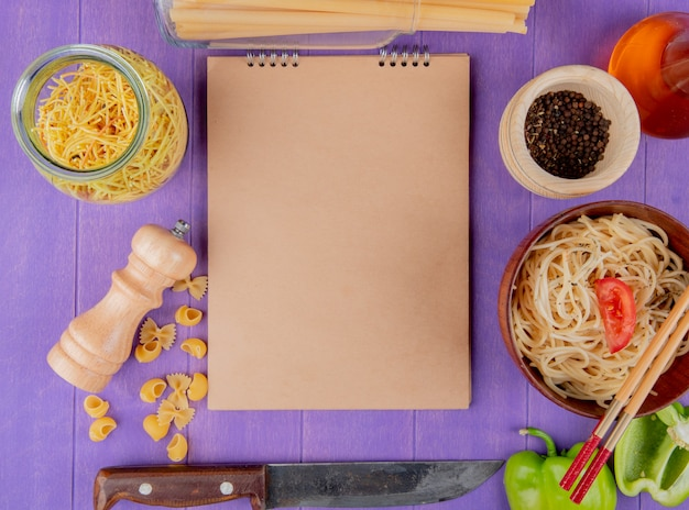 Top view of macaronis as cooked and uncooked spaghetti farfalle pipe-rigate bucatini with black pepper butter pepper knife around note pad on purple background with copy space