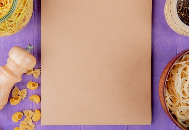 Top view of macaronis as cooked and uncooked spaghetti farfalle pipe-rigate with black pepper around note pad on purple background with copy space