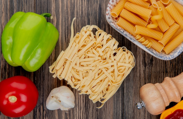 Vista dall'alto di maccheroni come tagliatelle ziti con pepe aglio sale pomodoro su legno