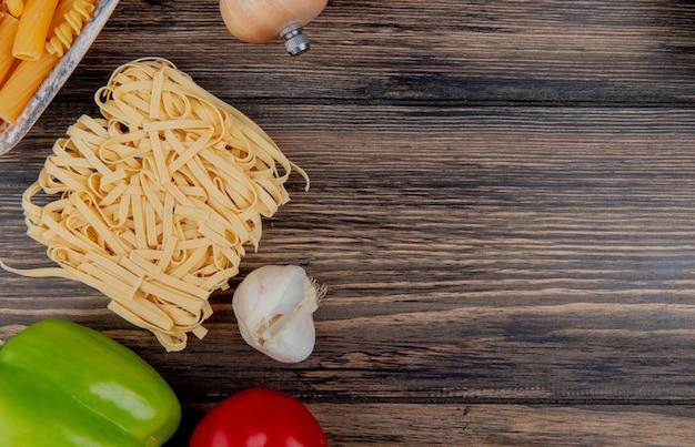 Vista superiore dei maccheroni come ziti di tagliatelle con il pomodoro dell'aglio del pepe su superficie di legno con lo spazio della copia