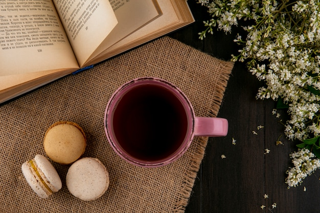 Top view of macarons with a cup of tea on a beige napkin with an open book and flowers