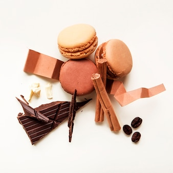 Top view of macaroons; roasted coffee beans; cinnamon and chocolate bar on white background