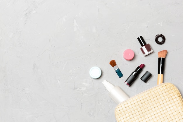 Top view of make up products fallen out of cosmetics bag on cement