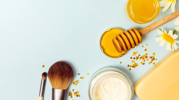 Top view of makeup brush; cream; honey; soap; bee pollen and white flower