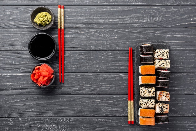 Top view maki sushi assortment on slate with chopsticks