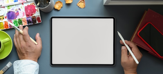 Top view of male artist working on his project on blank screen tablet in his creative studio