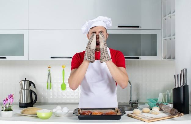 Top view of male chef wearing holder standing behind the table with pastries eggs grater on it and calling someone in the white kitchen