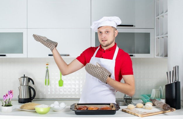 Top view of male chef wearing holder standing behind the table with pastries eggs grater on it and showing something on the right side in the white kitchen