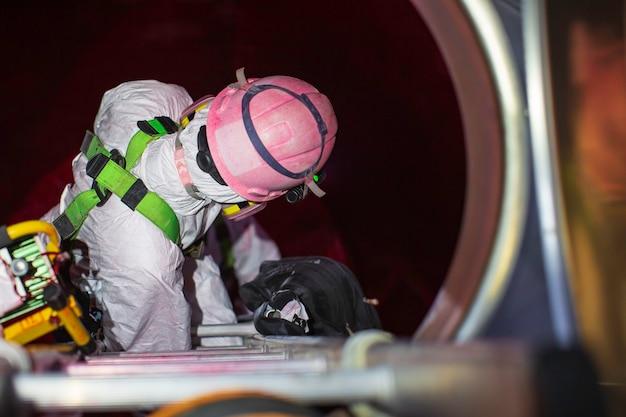 上面図男性が階段を上ってタンクのステンレス化学エリアに閉じ込められたスペース安全ブロワー新鮮な空気