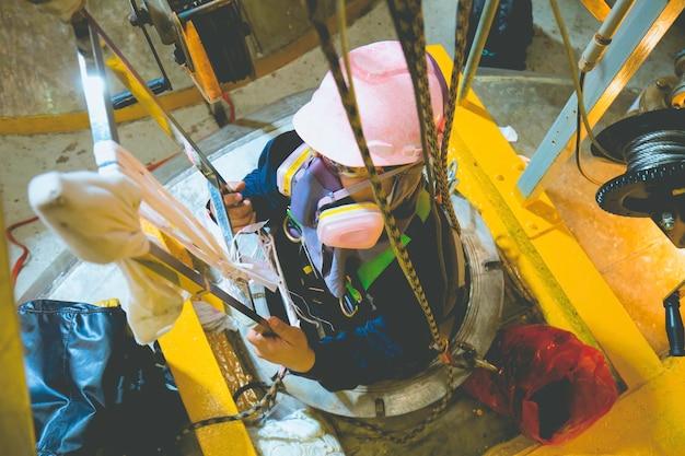 탑 뷰 남성은 탱크 스테인리스 화학 구역으로 계단을 올라 구조 로프 안전으로 생명을 구합니다.