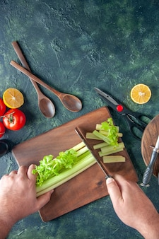 Vista dall'alto cuoco maschio taglio sedano su tavola scura insalata dieta pasto foto a colori salute alimentare
