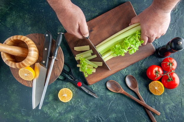 Top view male cook cutting celery on dark table salad diet meal color photo food health